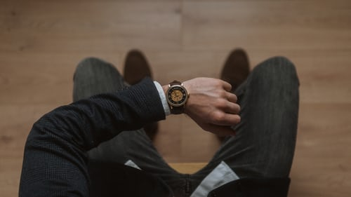 A man looking at his watch: Time, Hurry, Stress